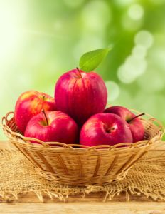 40129083 - apples in basket on wooden table over garden bokeh background